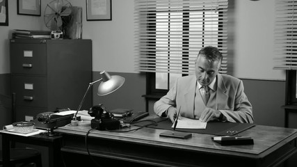 Vintage manager working at office desk checking paperwork.