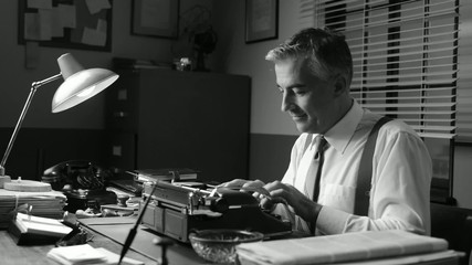 Smiling vintage reporter working at office desk and typing on a