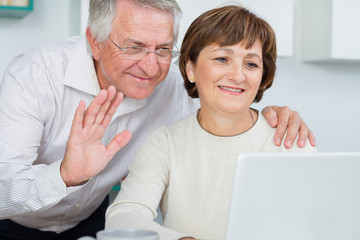 Seniors couple using a computer talking with video chat