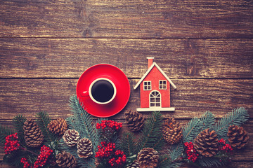 Coffee cup and toy house on a wooden table.