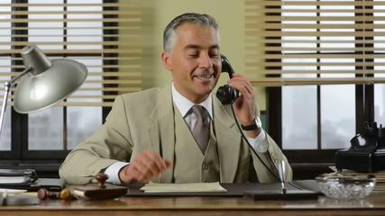 Confident handsome businessman working at office desk, talking o