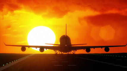 Plane lands on airport runway in front of large sunset