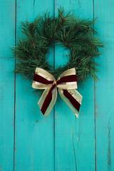 Christmas wreath hanging on antique teal blue wooden door