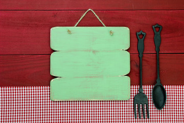 Blank green wood menu sign with cast iron spoon and fork