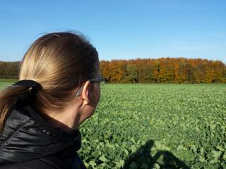 Frau blickt auf grünes Rapsfeld vor Herbstlandschaft