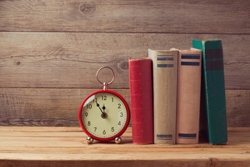 Vintage books and clock on wooden table