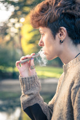 young girl smoking and relaxing in a park