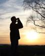 Mann schaut durch Fernglas bei einer Wanderung