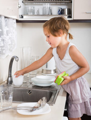Small child cleaning dishes