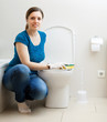 Smiling girl  cleaning toilet bowl