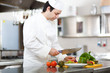 Friendly chef preparing vegetables in his kitchen