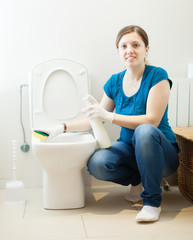 woman cleaning toilet bowl with sponge and cleaner