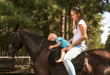 kid with mum drive on horse top