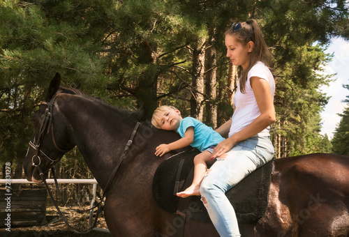kid with mum drive on horse top - 72831278