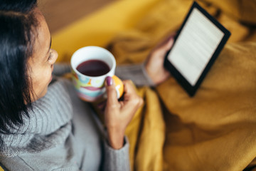 Young woman drinking tea reading ebook on couch