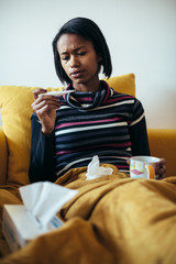 Sick young woman drinking tea on couch