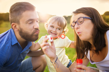 Little girl with parents blowing bubbles