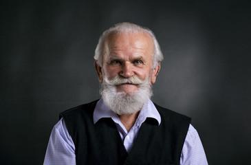 Old bearded man on black background