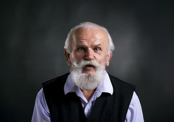 Old surprised bearded man on black background