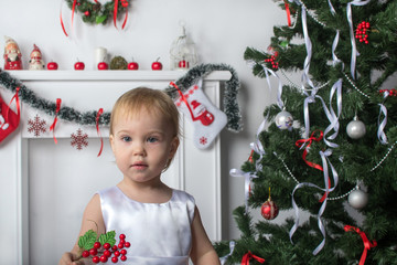 Cute little girl holds a red berries  near  New Year  Christmas