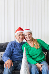 senior couple wear red santa christmas hat present
