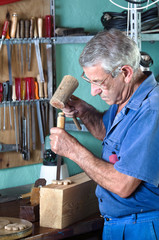 cabinetmaker carving wood with a chisel and hammer