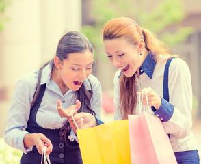 happy, laughing young shopper women outside shopping mall