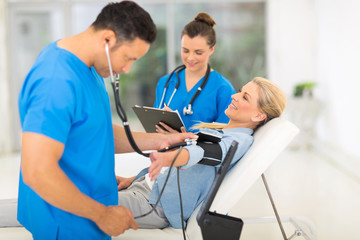 medical doctor taking mid age woman's blood pressure