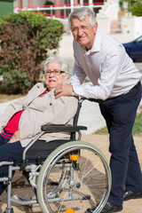 Man walking with senior woman in a wheelchair in park