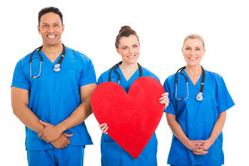young nurse holding heart shape with colleagues