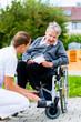Pflegerin hält Hand alter Frau im Rollstuhl