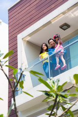 Asian family with child standing on home balcony