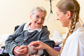 Pflegerin kümmert sich um Seniorin in Altenheim