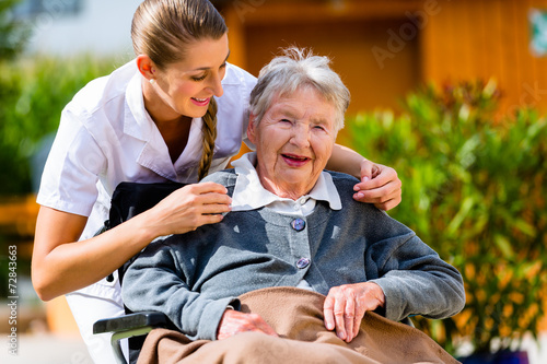 Leinwanddruck Bild Pflegerin hält Hand alter Frau im Rollstuhl