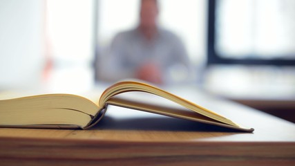 Book on table in front of businessman