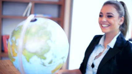 Young businesswoman with globe smiling