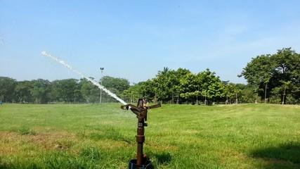 Watering sprinkler on grass field