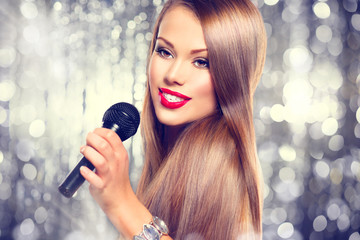 Singing woman. Beautiful girl singing over holiday background