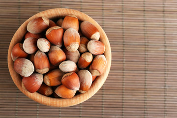 Hazelnuts in wooden bowl on bamboo mat background
