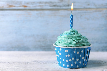 Delicious birthday cupcake on table on wooden background