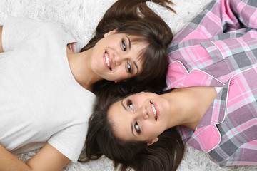 Beautiful girls twins in pajamas lie on carpet top view