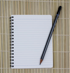 blank realistic spiral notepad notebook with pencil on brown bam