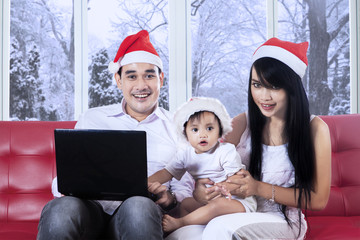 Cute girl in santa hat using laptop with family