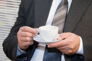 Male businessman relaxing with a cup in hands