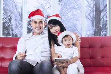Family with santa hat sitting on sofa