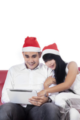 Romantic couple in santa hat using tablet