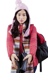 Student in warm clothes showing empty wallet