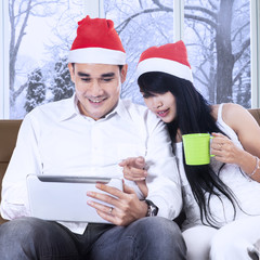 Woman in christmas hat pointing on tablet