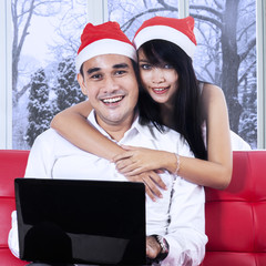 Woman in santa hat embrace her husband