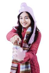 Young girl put coin into piggybank